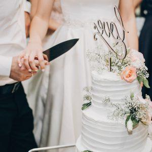 bride-and-groom-cutting-stylish-wedding-cake-at-wedding-reception.jpg