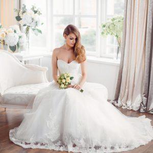 bride-in-beautiful-dress-sitting-resting-on-sofa-indoors.jpg